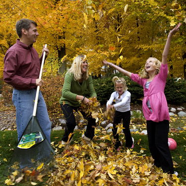 family raking leaves